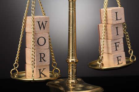 Foto de Close-up Of Golden Justice Scale With Wooden Blocks Showing Work And Life Text - Imagen libre de derechos