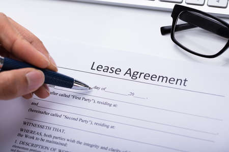 Photo pour Close-up Of A Person's Hand Filling Lease Agreement Form - image libre de droit