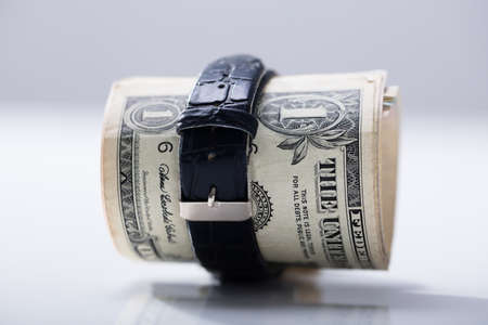 Foto de Rolled Up Dollar Banknote Tied With Belt Against White Background - Imagen libre de derechos