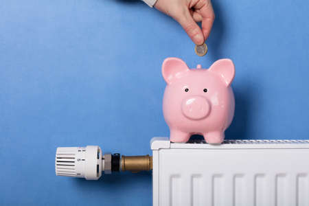 Foto de A Person's Hand Inserting Coin In Piggy Bank On Radiator - Imagen libre de derechos