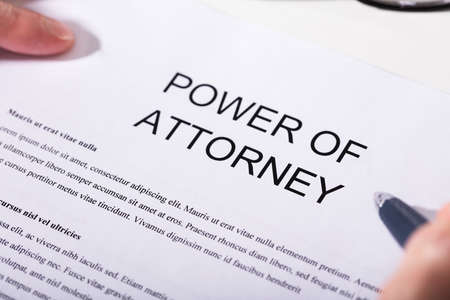 Photo pour Close-up Of A Person Holding Pen Over Power Of Attorney Form - image libre de droit