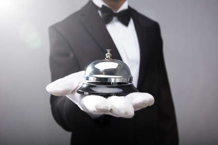 Photo pour Close-up of a waiter's hand holding service bell - image libre de droit