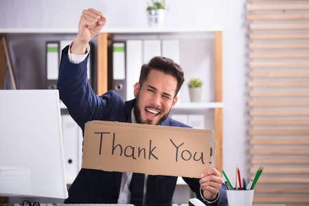 Foto de Smiling Young Businessman Raising His Arms While Holding Cardboard With Thank You Text - Imagen libre de derechos