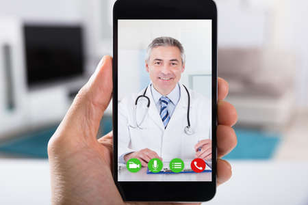 Photo pour Close-up Of A Person Video Conferencing With Happy Male Doctor On Smartphone - image libre de droit
