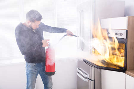 Foto de Young Man Using Red Fire Extinguisher To Stop Fire Coming From Oven In Kitchen - Imagen libre de derechos
