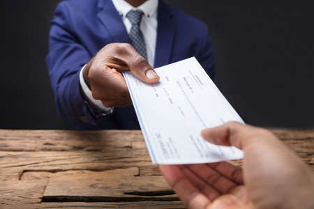 Photo pour Close-up Of A Businessman's Hand Giving Cheque To Colleague Over Wooden Desk - image libre de droit