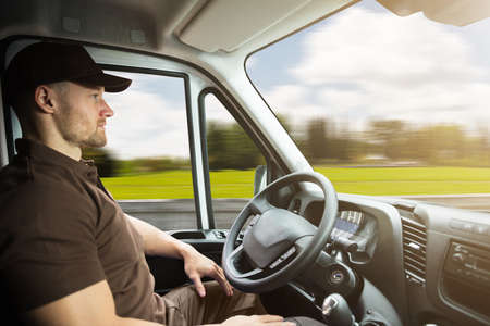 Photo for Portrait Of A Young Delivery Man Sitting Inside Self Driving Van - Royalty Free Image