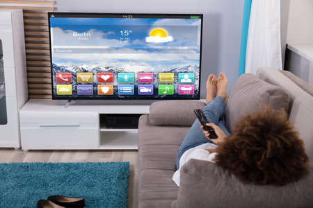 Photo for Woman Lying On Sofa Watching Television With Colorful Applications On Screen - Royalty Free Image