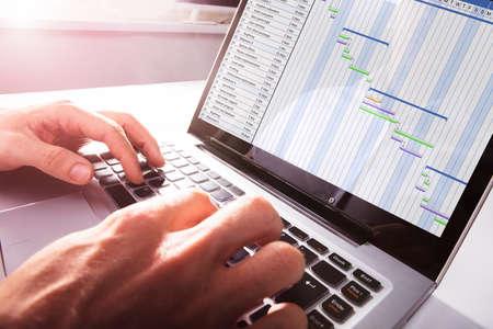 Foto de Close-up Of Businessman's Hands Working On Gantt Chart On Laptop At Office - Imagen libre de derechos