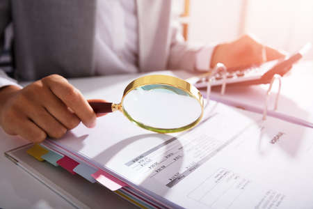 Photo for Photo Of Businesswoman Analyzing Invoice With Magnifying Glass - Royalty Free Image
