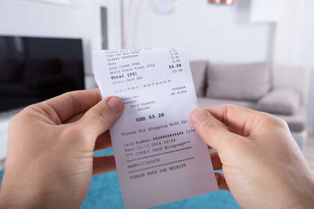 Photo for Close-up Of Person's Hand Holding Bill At Home - Royalty Free Image