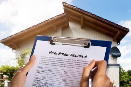 Foto de Person Filling Real Estate Appraisal Form In Front Of House - Imagen libre de derechos