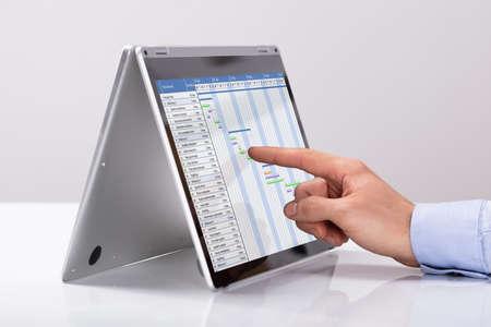 Foto de Businessman Pointing On Gantt Chart Over Hybrid Laptop At Workplace - Imagen libre de derechos