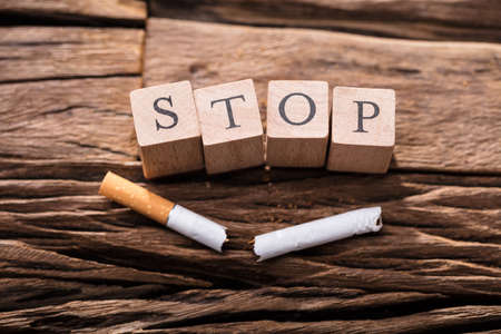 Foto de Close-up Of A Cigarette And Wooden Blocks Showing Stop Word On Desk - Imagen libre de derechos