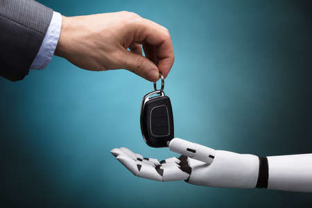 Photo for Close-up Of A Businessperson's Hand Giving Car Key To Robot On Grey Background - Royalty Free Image