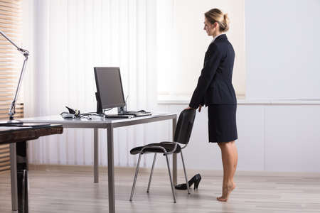 Photo for Young Businesswoman Stretching Her Legs At Workplace - Royalty Free Image