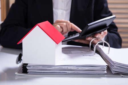 Foto de Businesswoman Calculating Financial Data With House Model On Desk - Imagen libre de derechos