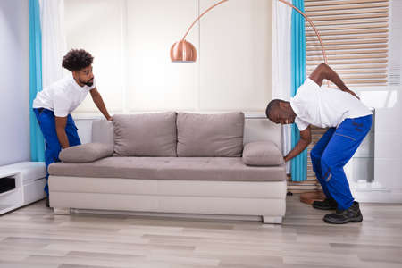 Foto de Young Male Movers With Backache Lifting Couch In The Living Room - Imagen libre de derechos