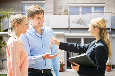 Photo for Female Real Estate Agent Giving House Key To Smiling Young Couple - Royalty Free Image
