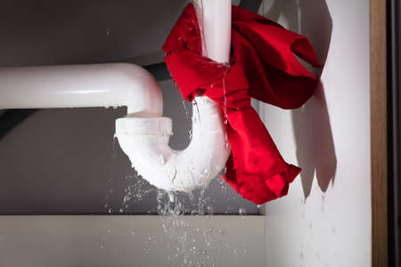 Foto de Close-up Of Red Napkin Tied Under The Leakage White Sink Pipe - Imagen libre de derechos