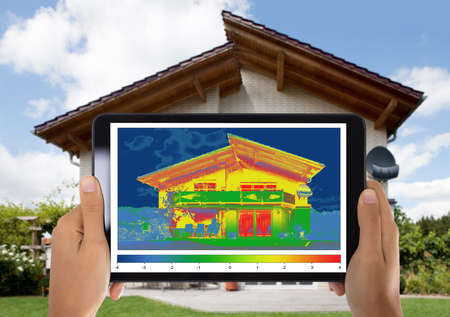 Photo for Close-up Of Person Detecting Heat Loss Outside The House Using Digital Tablet - Royalty Free Image