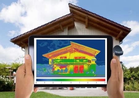 Foto de Close-up Of Person Detecting Heat Loss Outside The House Using Digital Tablet - Imagen libre de derechos