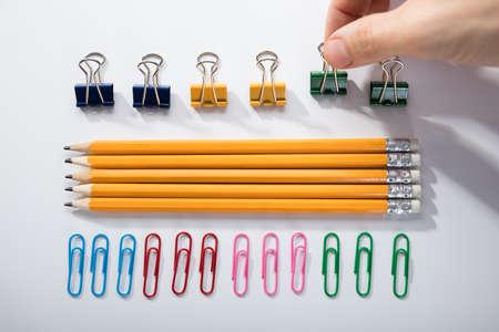 Foto de Person's Finger Arranging The Pencils With Row Of Pins Rubber And Pen On White Background - Imagen libre de derechos