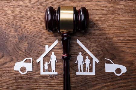 Photo pour Judge Mallet Between The Split Paper Cutout Family And Car On Wooden Desk - image libre de droit