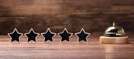 Foto de Black Five Stars Shape Arranged In Row With Service Bell On Wooden Table - Imagen libre de derechos