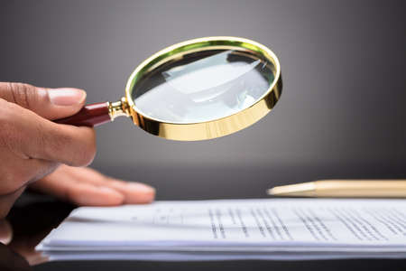 Photo for Close-up Of A Judge's Hand Looking At Document With Magnifying Glass - Royalty Free Image
