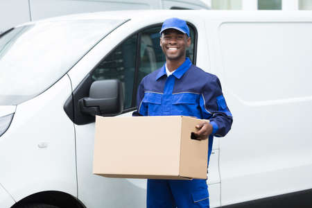 Photo for Delivery Man Standing Near The Van Holding Cardboard Box - Royalty Free Image
