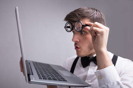 Photo for Young Man Looking At Laptop Screen Against Grey Background - Royalty Free Image