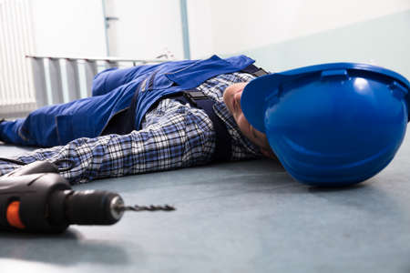 Photo pour Close-up Of Handyman's Helmet With Unconscious Handyman Lying On Floor - image libre de droit