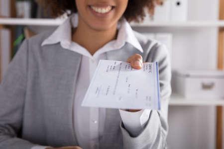 Photo pour Businessperson Hand Giving Cheque In Office At White Desk - image libre de droit