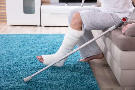 Foto de Young Man With Broken Leg Using Crutches To Get Up From Sofa - Imagen libre de derechos