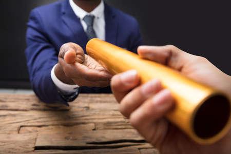 Photo pour Close-up Of A Businessman's Hand Passing Golden Relay Baton To His Partner - image libre de droit