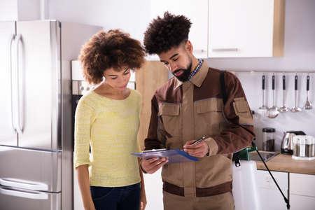 Foto de Young Male Pest Control Worker Showing Invoice To Woman In Domestic Kitchen - Imagen libre de derechos