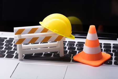 Photo for Road Barrier With Hard Hat And Traffic Cone On Laptop Keypad - Royalty Free Image