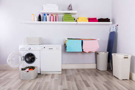 Photo pour Basket Full Of Dirty Clothes In Front Of Washing Machine At Laundry Room - image libre de droit