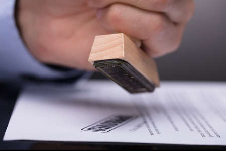 Photo pour Close-up Of A Businessperson's Hand Stamping Document - image libre de droit