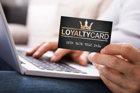 Photo for Close-up Of A Person's Hand With Loyalty Card Using Laptop - Royalty Free Image