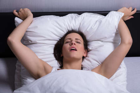 Photo pour High Angle View Of A Young Woman In Bed Getting Orgasm - image libre de droit