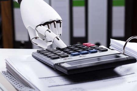Foto de Close-up Of A Robotic Hand Using Calculator - Imagen libre de derechos