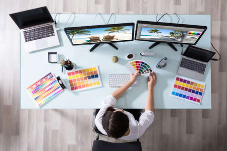 Photo for High Angle View Of A Female Designer Using Color Swatch While Working On Multiple Computer - Royalty Free Image