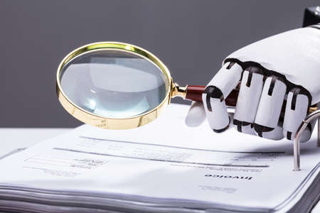 Photo for Close-up Of A Robotic Hand Holding Magnifying Glass Over Invoice At Workplace - Royalty Free Image