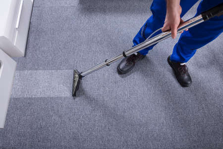 Photo for Janitor's Hand Cleaning Carpet With Vacuum Cleaner - Royalty Free Image