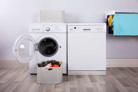 Photo for Empty Washing Machine With Pile Of Dirty Clothes In Basket At Laundry Room - Royalty Free Image