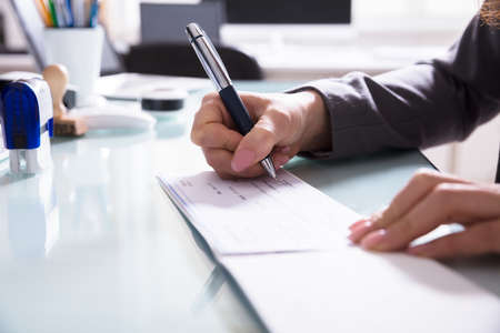 Foto de Close-up Of A Businessperson's Hand Signing Cheque With Pen In Office - Imagen libre de derechos