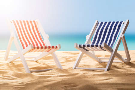 Foto de Close-up Of Two Blue And Red Striped Deck Chairs On Sandy Beach - Imagen libre de derechos