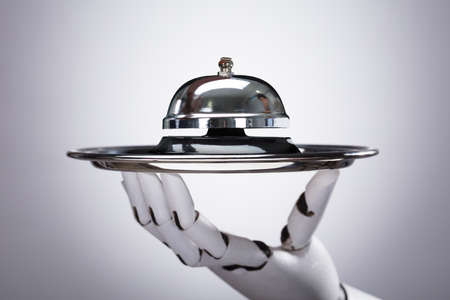 Photo pour Robotic Hand Holding Service Bell In Plate Against Grey Background - image libre de droit